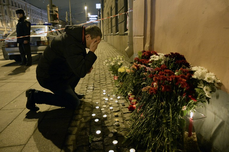 """A man reacts as he places flowers in memory of victims of the blast in the Saint Petersburg metro outside Technological Institute station on April 3, 2017. Ten people were killed and several more injured Monday after an explosion rocked the metro system in Russia's second city Saint Petersburg, and authorities launched a probe into suspected """"act of terror"""". / AFP PHOTO / Olga MALTSEVA"""